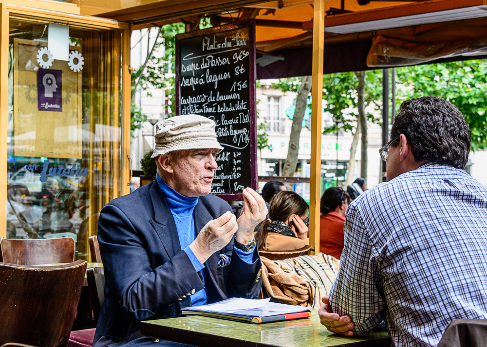 A gesture and decisive moment at a sidewalk cafe