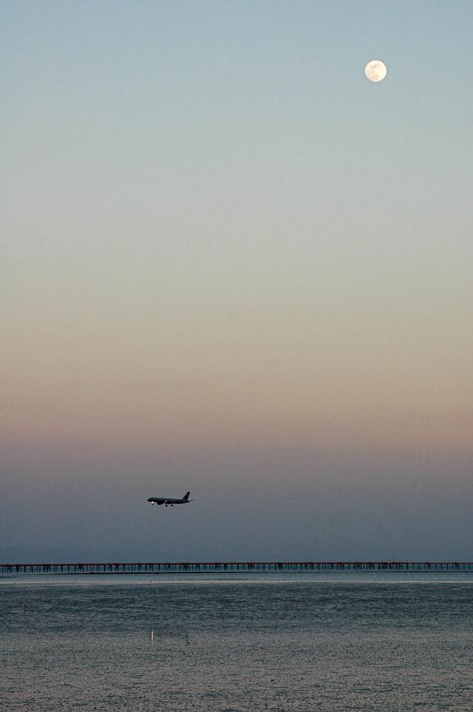 Airplane landing over water, moon